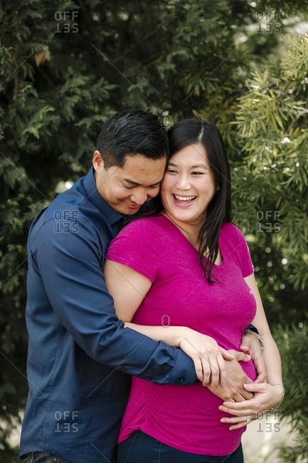 Loving man embracing pregnant woman at park