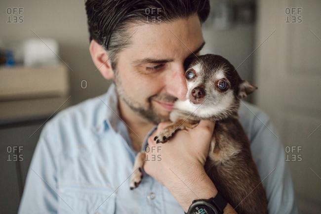 Close-up of man carrying Chihuahua at home