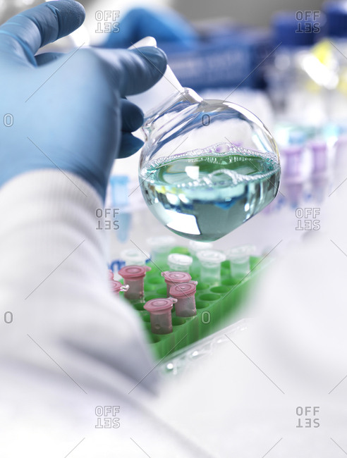 Cropped hand of scientist holding chemical in container for medical testing