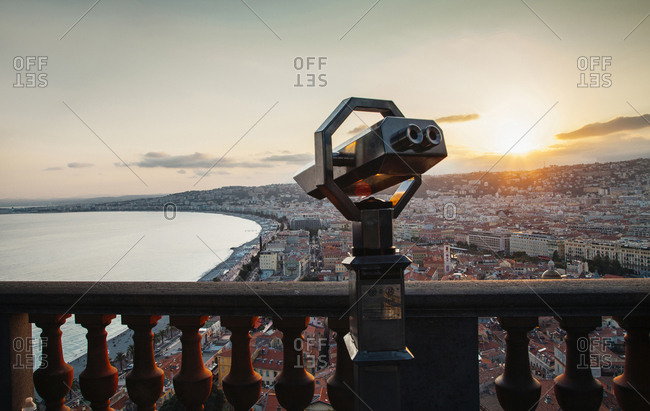 Coin-operated binoculars by balusters against cityscape and sky during sunset