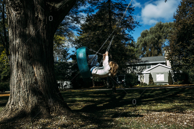 Playful girl swinging on tire Swing by tree trunk at park