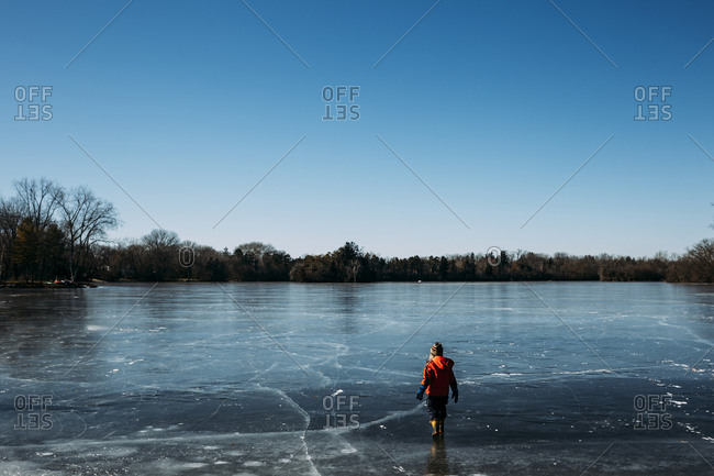 Rear view of carefree boy walking on frozen lake against clear sky during winter
