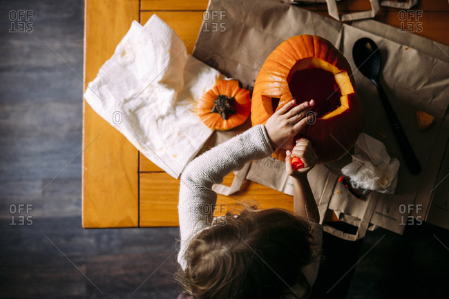 Overhead view of girl making jack o' lantern on table at home