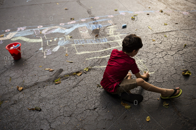 Full length of playful boy drawing with chalk on asphalt during autumn