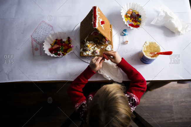 Overhead view of girl making gingerbread house on table at home