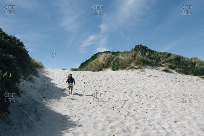 Rear view of girl running on sand at beach during summer