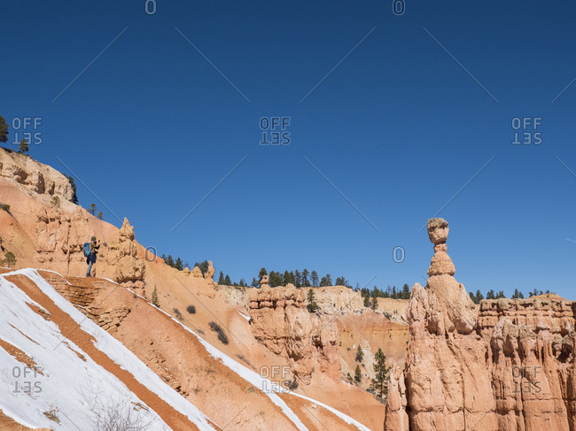 Mid distance view of hiker on rock formation against clear blue sky at desert