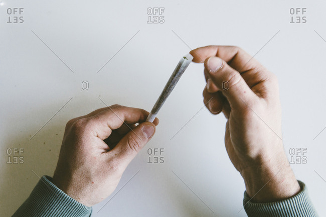 Cropped hands of man making marijuana joints over white table