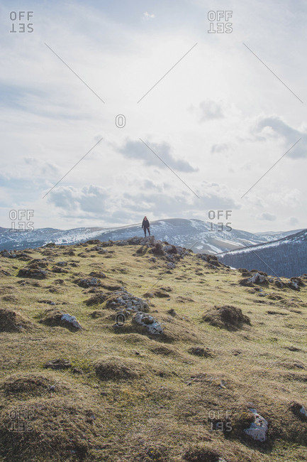 Mid distance view of hiker standing against mountains and cloudy sky during winter