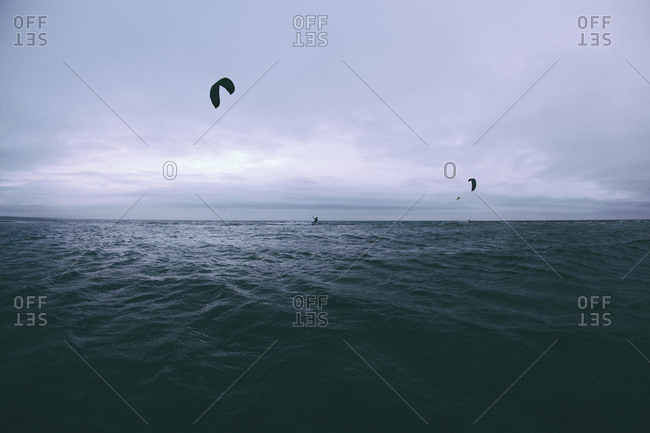 People kiteboarding over sea against cloudy sky