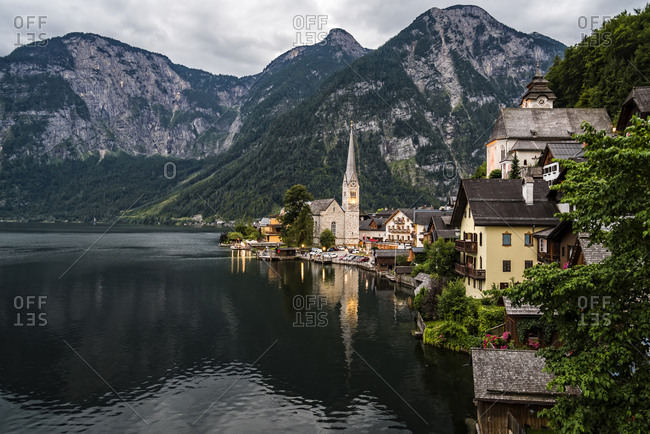 Houses and church by lake against mountains