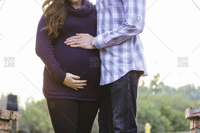 Midsection of husband touching pregnant wife's belly while standing against clear sky during sunset