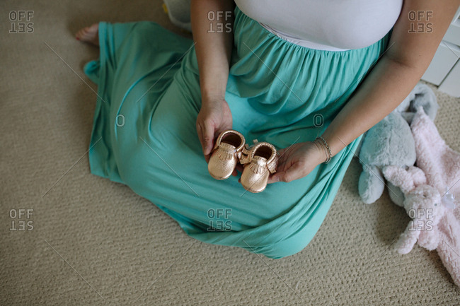 Low section of pregnant woman holding baby booties while sitting on carpet at home