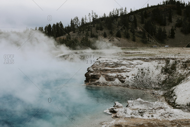 Smoke emitting from hot spring against mountain at Yellowstone National Park