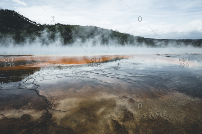 Scenic view of smoke emitting hot spring against mountains at Yellowstone National Park