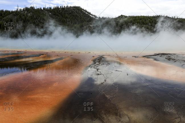 Idyllic view of smoke emitting hot spring against mountains at Yellowstone National Park
