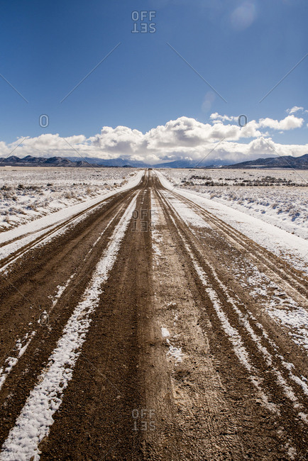 Dirt road amidst snowy desert against sky during winter