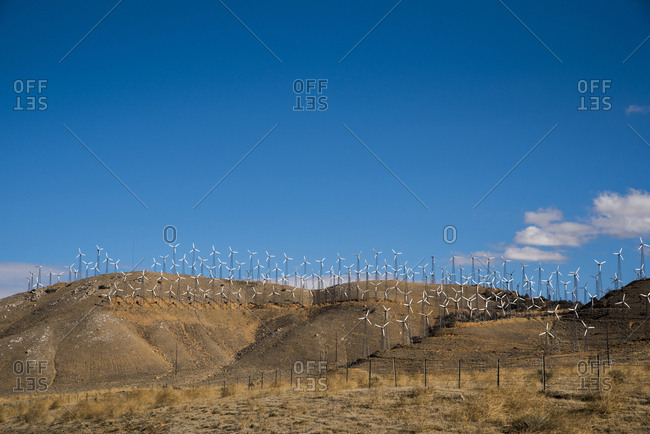 Windmills on mountains at desert against blue sky