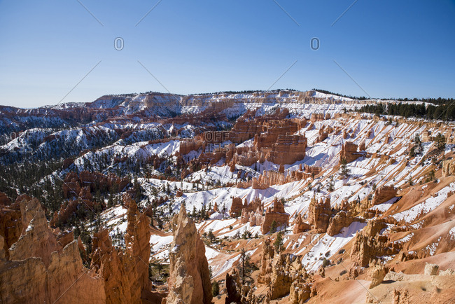 Scenic view of rock formations on snowy desert against clear sky during winter