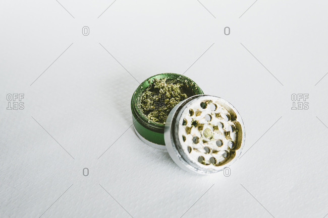Close-up of marijuana in grinder on white table