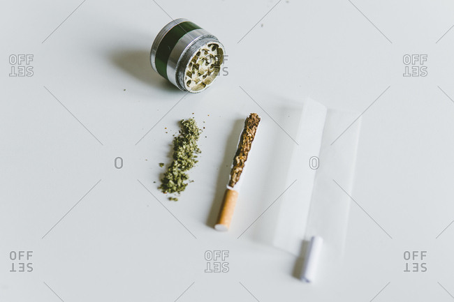 Overhead view of marijuana joints, cigarette with paper and grinder on white table