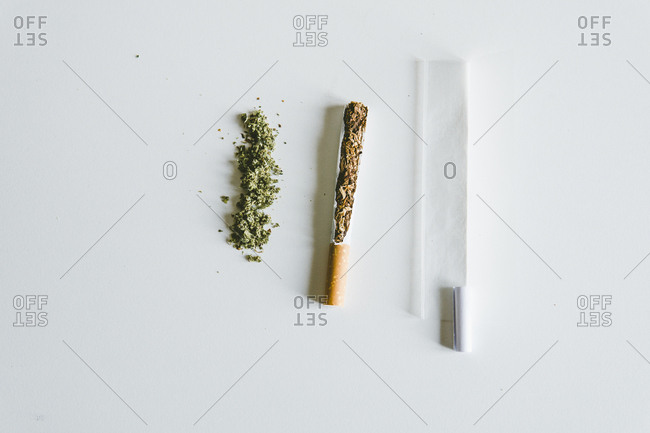 Overhead view of marijuana joints and cigarette with paper on table