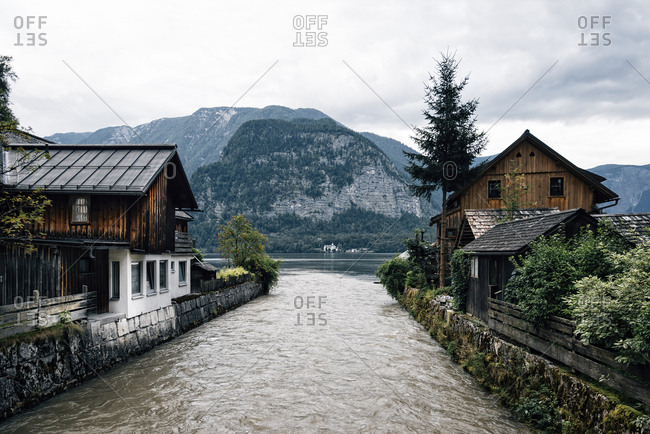 Lake flowing amidst houses against mountains in village