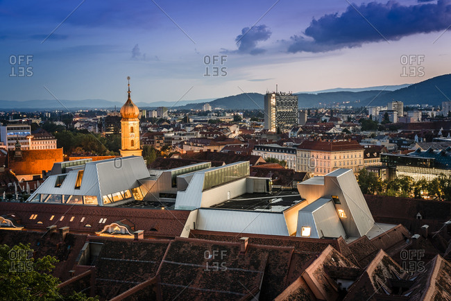 Cityscape against cloudy sky from Schlossberg at night