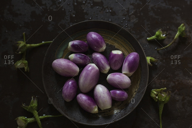Close-up of fresh eggplants in plate on wet metallic table