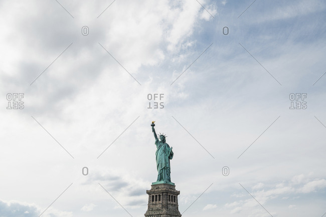 Low angle view of Statue of Liberty against cloudy sky in city