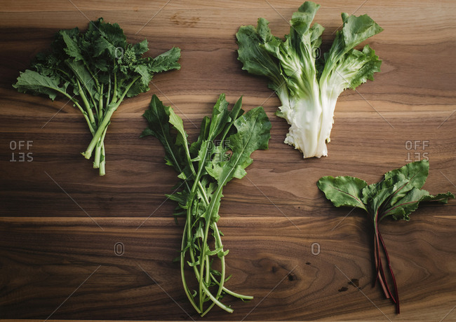 Overhead view of various leaf vegetables on wooden table