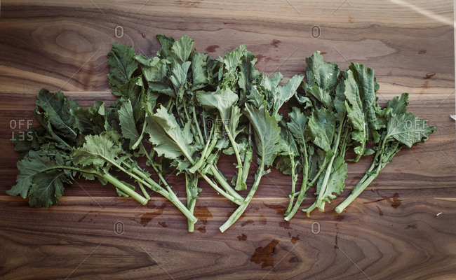 Overhead view of fresh turnip leaves on wooden table
