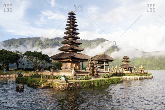 Bratan, Bali, Indonesia - January 25, 2013: Pura Bratan water temple on lake Bratan with clouds shrouding mountains in background