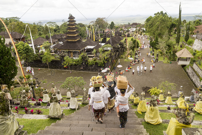 Looking down on procession of worshippers carrying offerings as they descend the stairs of Besakih Temple in Bali, Indonesia