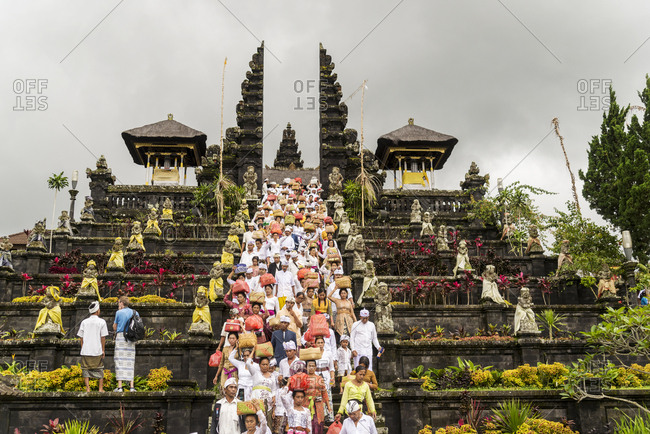 Besakih, Bali, Indonesia - January 29, 2013: Procession of worshippers fill the stairs as they descend from Besakih Temple