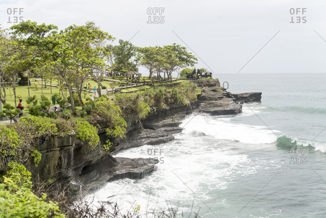 Bali, Indonesia - February 1, 2013: Waves crashing against cliffs at base of Tanah Lot Temple grounds