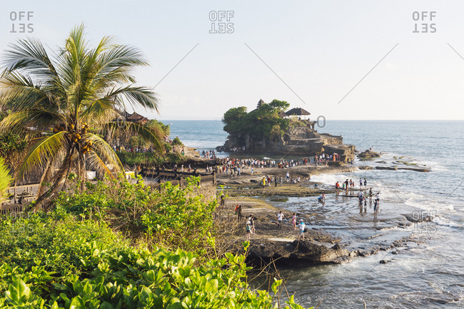 Tanah Lot, Bali, Indonesia - February 08, 2013: Visitors crowd the rocks around Tanah Lot Temple