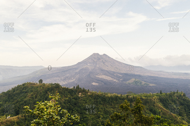 View over lush greenery towards arid lunar landscape of Mount Agung in Bali, Indonesia