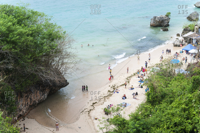 Padang Padang, Bali, Indonesia - January 20, 2013: Looking down at visitors on narrow strip of sand at Padang Padang Beach