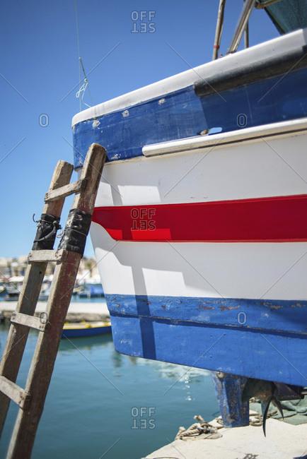 Ladder propped against corner of striped boat