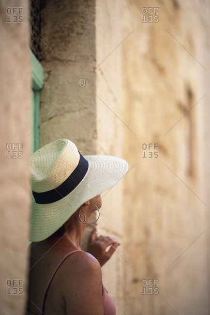 Back side of woman in large hat looking upwards in shaded alley