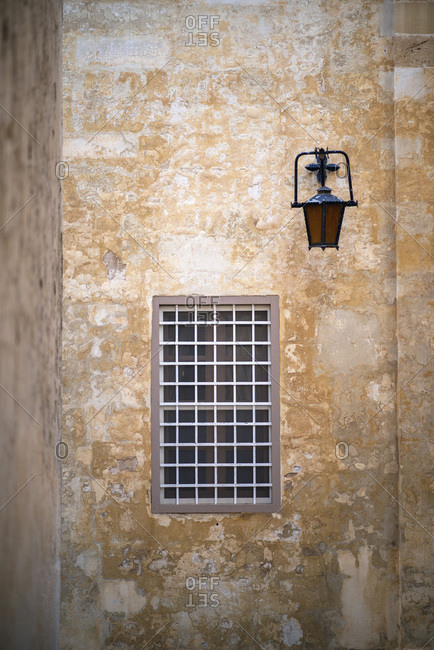 Rustic building exterior corner with hanging lantern above window