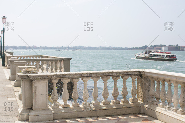 Water taxi cruising by old railings near Biennale, Venice, Italy