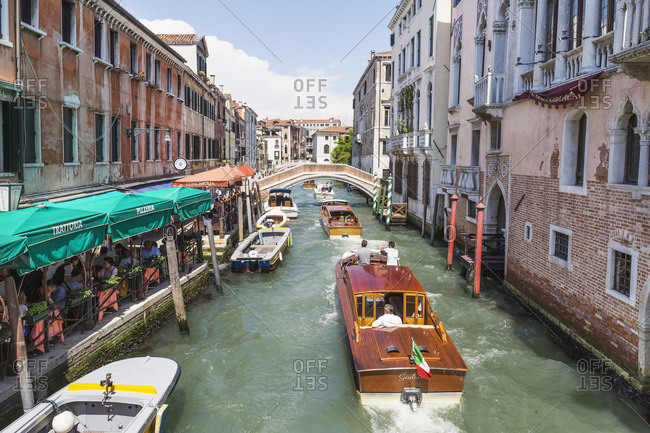 Venice, Italy - May 13, 2018: Wooden power boats going down busy canal along restaurants