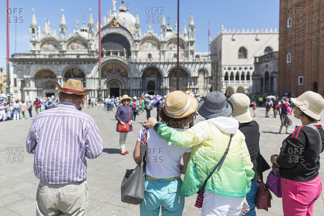 Venice, Italy - May 13, 2018: Group of Asian tourists taking pictures of a friend posing in busy St. Mark's Square