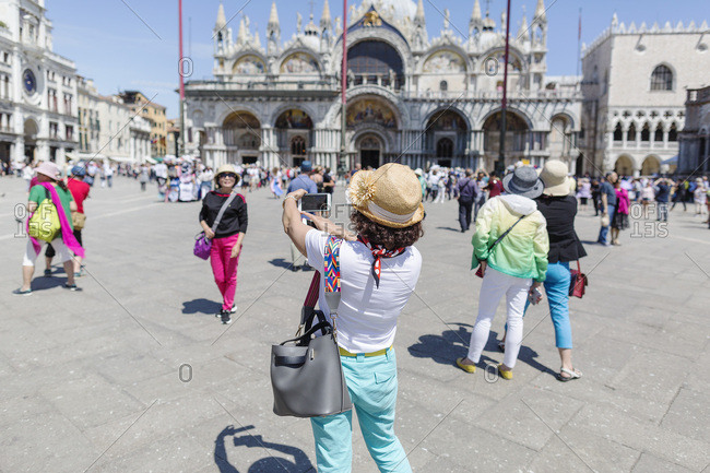 Venice, Italy - May 13, 2018: Woman taking a picture of her friend in busy St. Marks Square