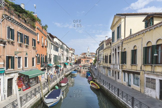 Venice, Italy - May 13, 2018: Tourists walking along quiet boat-lined canal