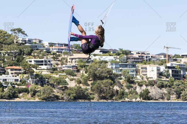 A young woman kite boards on the Swan River in Perth Western Australia