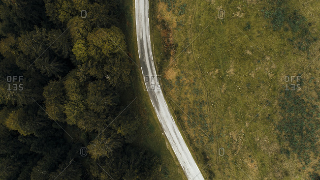 Top view of curved road between forest and empty field