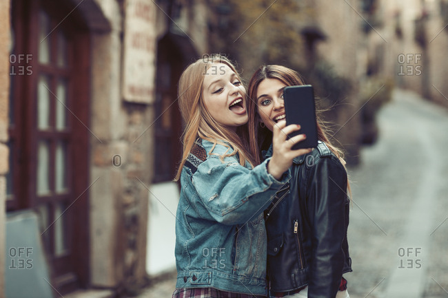 Young women stopping for a selfie in quaint village